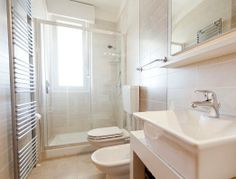 Bathroom with shower, toilet, bidet and wash basin.