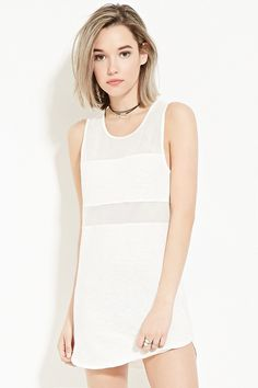 A sleeveless slub knit dress featuring a mini length, a mesh-paneled design, and a vented curved hem.
