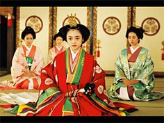 A woman dressed in junihitoe as well as several  more in modern kimono.