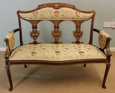 Antique Edwardian Inlaid Sofa Settee. This Antique Edwardian marquetry inlaid mahogany two seater sofa settee has a inlaid and shaped back with a padded arms, back and seat the shaped front and legs have inlaid decoration.