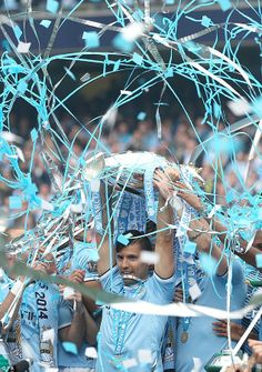 Tickertape: Sergio Aguero lifts the trophy for the second time amid a rain of blue and white ribbons #PremierLeague2013/14