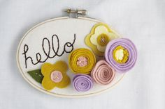 "This pastel custom wall art features hand-cut and hand-stitched felt flowers and a custom message or name so that your wall art makes your little girl feel loved and oh-so-special.    ""hello"" (or a name or word of your choice) is hand-embroidered in chocolate brown embroidery thread on cotton duck cloth and adorned with wool felt flowers in lilac, ochre yellow, ginger and butter.    Part of the VINTAGE BLOOMS collection, this felt wall art is framed by a wooden embroidery hoop with a natural…"