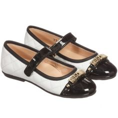 Girls black and white leather pump-style shoes by Moschino Kid-Teen. Made in white quilted leather, with black patent toes and cushioned insoles for comfort and support. Fastening with a velcro strap, they have a gold metal logo across the toe and a soft, black rubber sole with a red logo heart.
