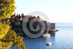 Photo about Old buildings of the small island of Sveti Stefan Saint Stephen with small boats near some trees. Image of city, small, walls - 92517255 Saint Stephen, Small Boats, Small Island, Old Buildings, Saints, Trees, Symbols, Stock Photos, City
