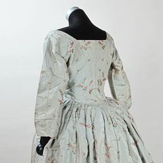 Rear view, robe à l'anglaise with quilted petticoat, worn: United States, fabric: probably Spitalfields/ England, c. 1775. Sage green silk embroidered with a pattern of floral sprays and sprigs featuring roses, cotton lining; petticoat: robin`s egg blue silk with a trapunto-quilted diamond pattern covering the upper area of the petticoat, and a band of trapunto featuring urns with floral bouquets, floral festoons and wreaths in a field of tiny quilted diamonds above the hemline.
