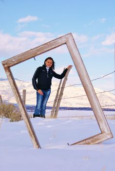 Senior photo shoot in the snow through an empty frame (or in this case an old window pane).