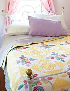 A soft, buttery yellow teamed with solid white in this bed-size quilt  provides the perfect background for the bright '30s print appliqués.