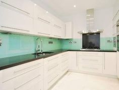 photo of modern mint green turquoise white frosted glass kitchen with glass splashback white kitchen cabinets