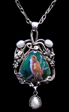 Bromsgrove Guild. An Arts and Crafts silver pendant inset with an enamel of a bird set within a wirework surround of leaves to a handmade silver chain. English, c. 1900. Size: Length with bale 6 cm. Width 3 cm. Sold by Van den Bosch.