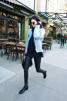 March 29, 2016 Running around downtown NYC, Jenner layers a hoodie under a distressed denim jacket, pairing one of our go-to combos with leather leggings and boots.