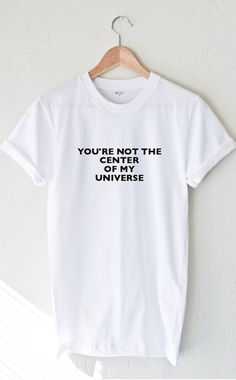 """- Description Details: Unisex, loose fit short sleeve t-shirt in white with print featuring 'You're Not The Center Of My Universe'. Brand: NYCT Clothing. Measurements: (Size Guide) S: 36"""" bust, 27"""" le"""