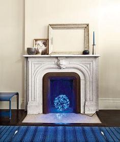 A surprising way to bring a glow to the fireplace—and especially striking against a shiny floor.