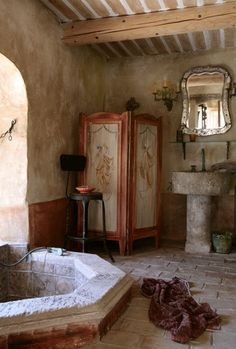 Marbled walls. Stone floors. Tiled, in ground bath tub. Large window. Muslin curtains. Free standing sink. Sit down vanity. Sconces.