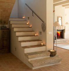 Escalera de obra con barandilla empotrada metálica y velas en los peldaños