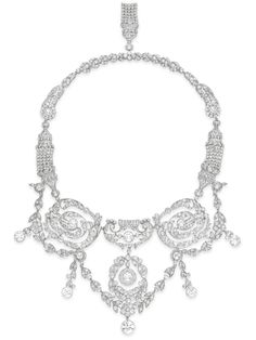 A BELLE EPOQUE DIAMOND NECKLACE  The front suspending an old European-cut diamond foliate festoon, designed as four openwork old European-cut diamond plaques, each centering upon a collet-set diamond, suspending an old European-cut foliate swag, with a graduated fringe of five collet-set diamonds, to the pierced old European-cut diamond foliate neckchain, the clasp decorated with an old European-cut diamond tassel, mounted in platinum, circa 1905, 16¼ ins.  Price Realized   $98,500  Estimate…