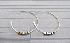 These lovely sterling silver open hoop earrings have pewter coloured beads threaded on them. The 925 hoops have been hand forged by myself and the beads are free-moving on the earrings.  The hoops measure 32mm (1.25 inches) and the beads are 2.5mm each. As the beads are free moving they are secured by the width of the silver on one end and by a silicone stopper at the other. The earrings are completely hand made - they have been shaped, hammered and tumbled to give a high shine and extra…