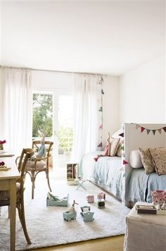 back to back beds on against a long wall, bentwood x-back chairs, bunting, french doors, and natural light.