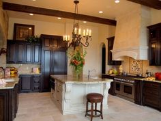 Black cabinets, cream walls and island, chandelier