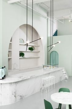 The Budapest Café in Chengdu, China, by Biasol studio is inspired by film director Wes Anderson's style - Huskdesignblog | Wes Anderson decoration | Biasol design studio | green interior | green walls | 2018 interior design trends | green-toned interior | modern café | contemporary café | sculptural interior | minimalist architecture | green chair | pink seating | marble counter | arches | minimal lighting fixtures | China coffee shop | millennials place | instagram interior...