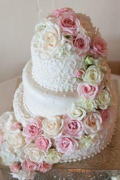 Elegant three tier wedding cake with cascade of fresh flowers