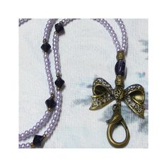 """Lanyard Necklace - Bronze Bow Charm by The Kennett Collection Beaded lanyard to hold keys, id/security badges/passes etc.Length is 80 cms (31"""") to the lariat, which is 7cms (3"""") long.It will slip over the head, and has a toggle clasp.These can be custom made for you, so if you would likea different length or clasp, please ask.No extra charge for this service.Features a bronze filigree lace bow charm - 3-5cm (1.5 to 2""""), and.35mm (1.5"""") long lanyard clasp.4mm glass pearls and antique bronzed…"""