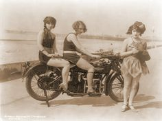 vintage motorcycle and three women on the beach