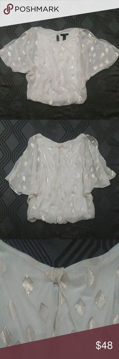 White House Black Market Cold Shoulder Silk Blouse White House Black Market Cold Shoulder Silk Blouse sz XS. Pre-owned excellent condition with beautiful silver embellishments. It is stunning. It has a cute eye hole in the back of the neck, and an elastic band at the waist. White House Black Market Tops Blouses
