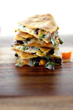 BUTTERNUT SQUASH, BLACK BEAN, AND ROASTED POBLANO QUESADILLAS 4 poblano chiles 4 cups butternut squash, peeled, seeded, and diced into 1/2-inch pieces 3/4 cup red onion, diced 1 can black beans, drained and rinsed 1/2 cup chopped fresh cilantro 1 cup Pepper Jack cheese, shredded 8-12 corn tortillas Serve with fresh salsa and lime wedges