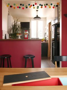 Design Sponge/ Image above: Bar and kitchen. The table top of the Hansen Family dining table has two cases to either hide or present things....