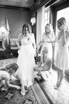 bridesmaids helping the bride with her dress and shoes before the wedding