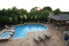 What better place for outdoor entertainment than a pool? This space has it all: pool, outdoor kitchen and living space. By Outdoor Signature in Argyle, TX