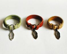 SOMETHINGMONUMENTAL on Etsy  leather ring with feather charm