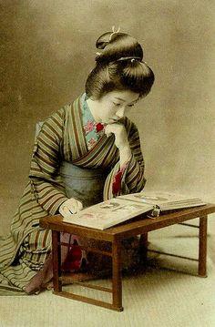 GEISHA LOOKING AT PHOTOGRAPHS