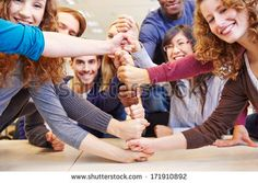 Students stacking fists for cooperation and teamwork in a university - stock photo