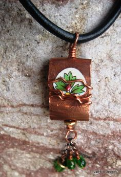 """Etched copper has been folded to form this prayer pendant. Prayer Package pendants are based on the Tibetan prayer wheel. The word """"Joy"""" is stamped inside the pendant and is activated with each breath much like spinning the wheel sends out the prayers. A piece of vintage tin in a leaf pattern adorns the front of the pendant. The piece is wire wrapped together and hangs from a black 4mm leather cord. You will decide the length of the cord."""