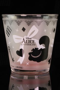 """Alice in Wonderland Tumbler  Alice is surrounded with spades, hearts, clubs and diamonds reflective of the playing card characters she meets down the Rabbit Hole. In all his grinning gloriousness, the Chesire Cat graces the back of the glass. 12 oz Alice in Wonderland tumbler measures 3 1/4"""" inches at it's widest, 3 1/4"""" tall."""