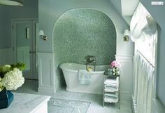 source: Courtney Hill Interiors    Master bathroom with spa-like tub alcove, freestanding tub, Waterworks Easton Etagere with Clear Glass, blue paint color, marble tiles floor with mosaic inset tiles, cafe curtains and mirrored French doors. (window treatments)