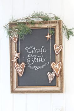 Cute way to decorate a framed picture or chalkboard for Christmas: drape it with greenery and gingerbread cookies.