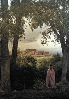 A Taos Indian pueblo rests on the hill behind women in the foreground. New Mexico, USA~Autochrome by Franklin Price Knott,1920s.
