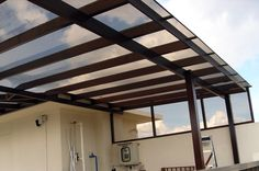 Polycarbonate patio or deck roof. Let's light in, protects from rain. Modern design. Comes in clear or black and I'm kinda liking the black.