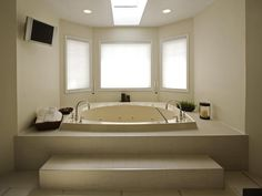 Step-up sunken bathtub.  Is that a TV on the wall?  I love the grace and simplicity of this area.