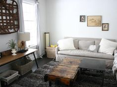 Rebekah Zaveloff designed this casual family room with a comfortable sofa, rustic factory-cart coffee table, antique tobacco basket and vintage accessories. The warm neutrals and cool grays combine for a clean, comfortable look.