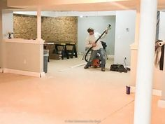 Basement remodel with vinyl flooring over concrete, planked ceiling, half wall to create separate spaces in a large basement with white columns. Blue Grey Walls, Grey Wall Color, Oak Color, Basement Renovations, Basement Ideas, Blogger Home, Plank Ceiling, Half Walls, Vinyl Plank Flooring