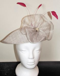 This is a pretty handmade teardrop style fascinator on a silver sinamay base. The fascinator is decorated with a large silver flower with hand stitched cream pearls and fuschia pink coque feathers. The fascinator has elastic to enable you to attach it to your head. Other sinamay colours are available.  There is currently 1 item in stock in silver, which can be shipped within 1 - 2 business days. However, if you require any other colour, please allow 1 - 2 weeks for me to make this.  The…