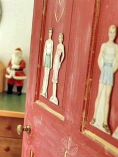 Vintage paper dolls set against a bright red painted door welcome guests to the bathroom.