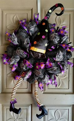 This is a gorgeous Halloween Witch deco mesh wreath made of black and silver striped mesh and accented with purple, orange, green, black polka dot ribbon and spiderweb glittery ribbon and a cute plush