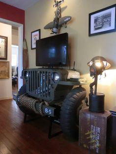 Jeep furniture for man cave - WWII Jeep Entertainment Center (Blu-ray on lower shelf), tv mount, or console table. Recycled from Willys and Ford parts - made by Jason Barnett - http://www.jasonbarnettartist.com/blog/ - mancave ideas - decor - creepy lamp is WWII gas mask