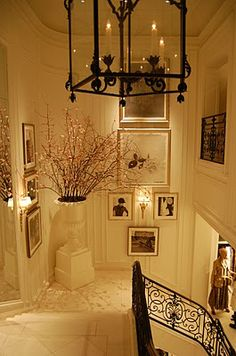 Beautiful stairwell in white with black accents in light fixture, prints, railing and hint of color in the floral branches