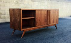 a mid century modern low audio video credenza. Made out of solid and furniture grade walnut ply. 2 sliding doors and 1 adjustable shelf per opening. (hinged door available as well). Has a hand applied oil / poly blend finish. Dimensions 60x 16x 23.5  Custom sizing, materials, etc. available  Shipping cost is $290.00 Contact for local delivery.  Lead time varies depending on work load. (Usually 7-12 weeks)  I handpick all wood for each project, but due to wood being a natural product it…