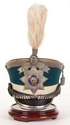 AN IMPERIAL RUSSIAN PETERBURGSKI GUARD INFANTRY REGIMENT OFFICER'S SHAKO OR KIVER, Model 1907. 'Bell crown' shako with black leather top, royal blue wool rise, white band, yellow piping and black leather visor. Has silvered and enamel Guard Star plate, FOR DISTINCTION bandeau, silvered chin scales and visor trim, and a cockade with white horsehair plume. Complete with silver bullion crown braid, cord and tassel. Lined in white silk and a leather sweatband. - Jackson's International…